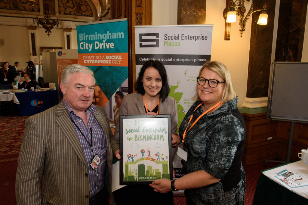 Sarah Crawley presenting Councillor Tony Kennedy and Jennie Assersohn; Community Investment Manager for Wates, with iSE's biodegradable seeded paper